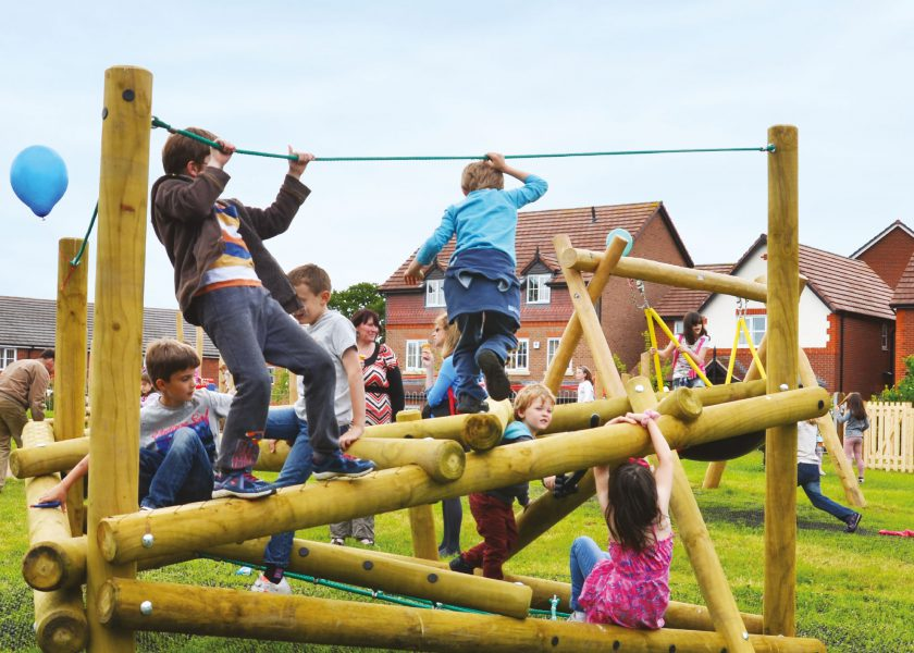 Children playing laughing on timber clamber stack green grass sunny weather