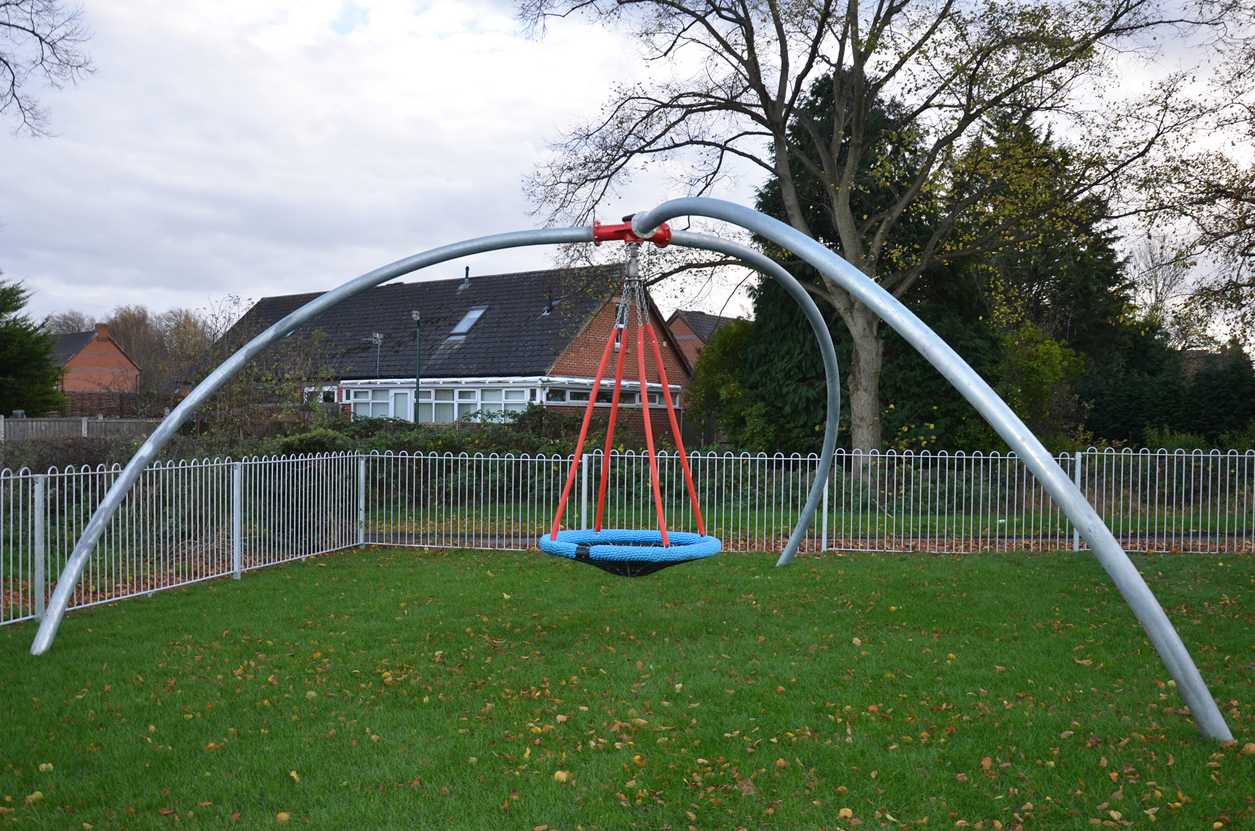 the inclusive single point swing has a blue basket seat hanging on chain from a central red pivot held by three curved silver legs, it is sat above grass with a surrounding silver fence with a house and trees in the background