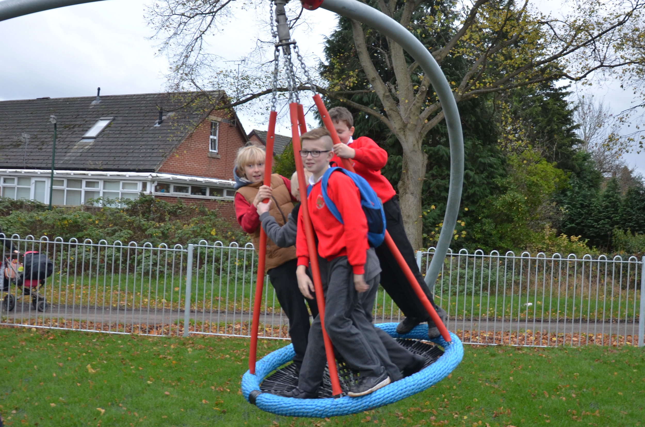 the inclusive single point swing, three children stand in the blue basket seat hanging on chain from a central red pivot held by three curved silver legs, it is sat above grass with a surrounding silver fence with a house and trees in the background