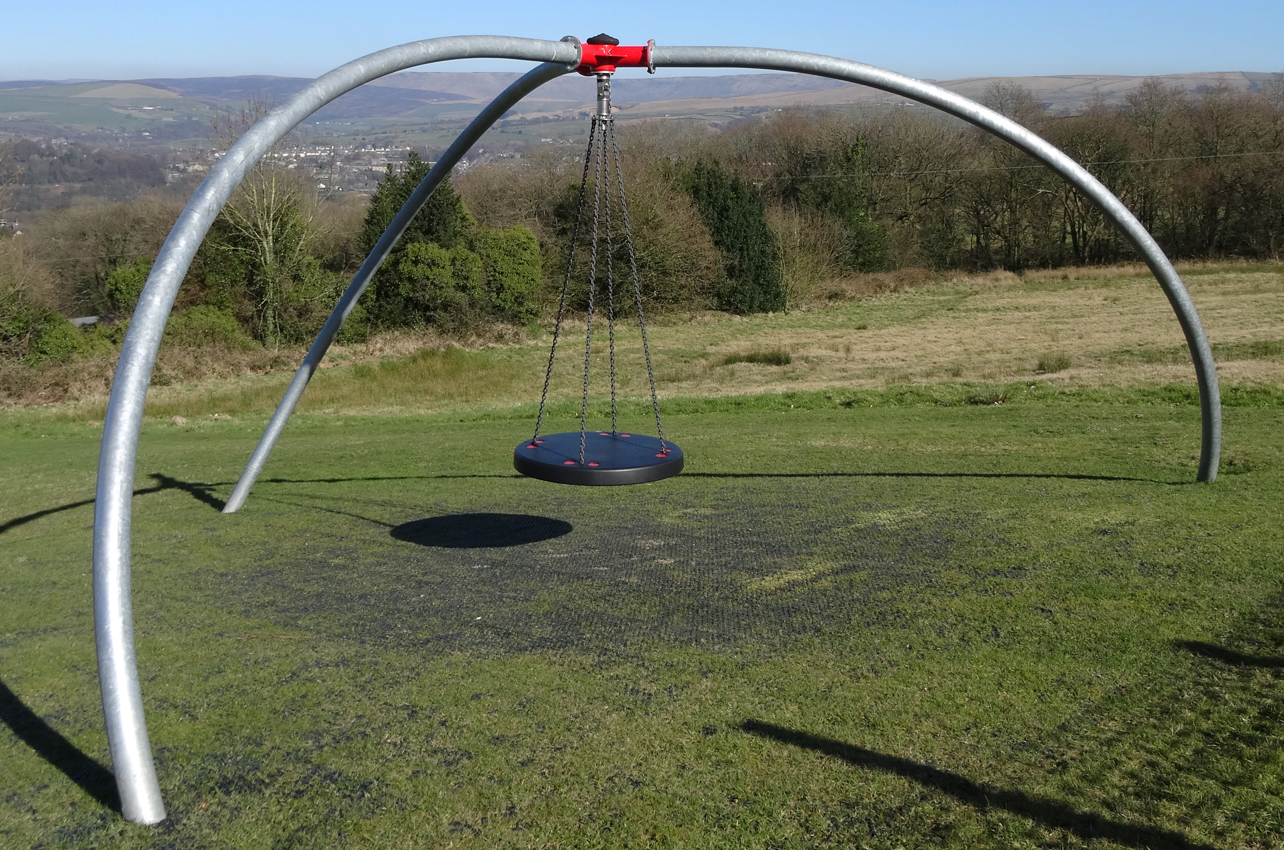 the inclusive single point swing has a flat swing hanging on chain from a central red pivot held by three curved silver legs, it is sat above grass with trees in the background