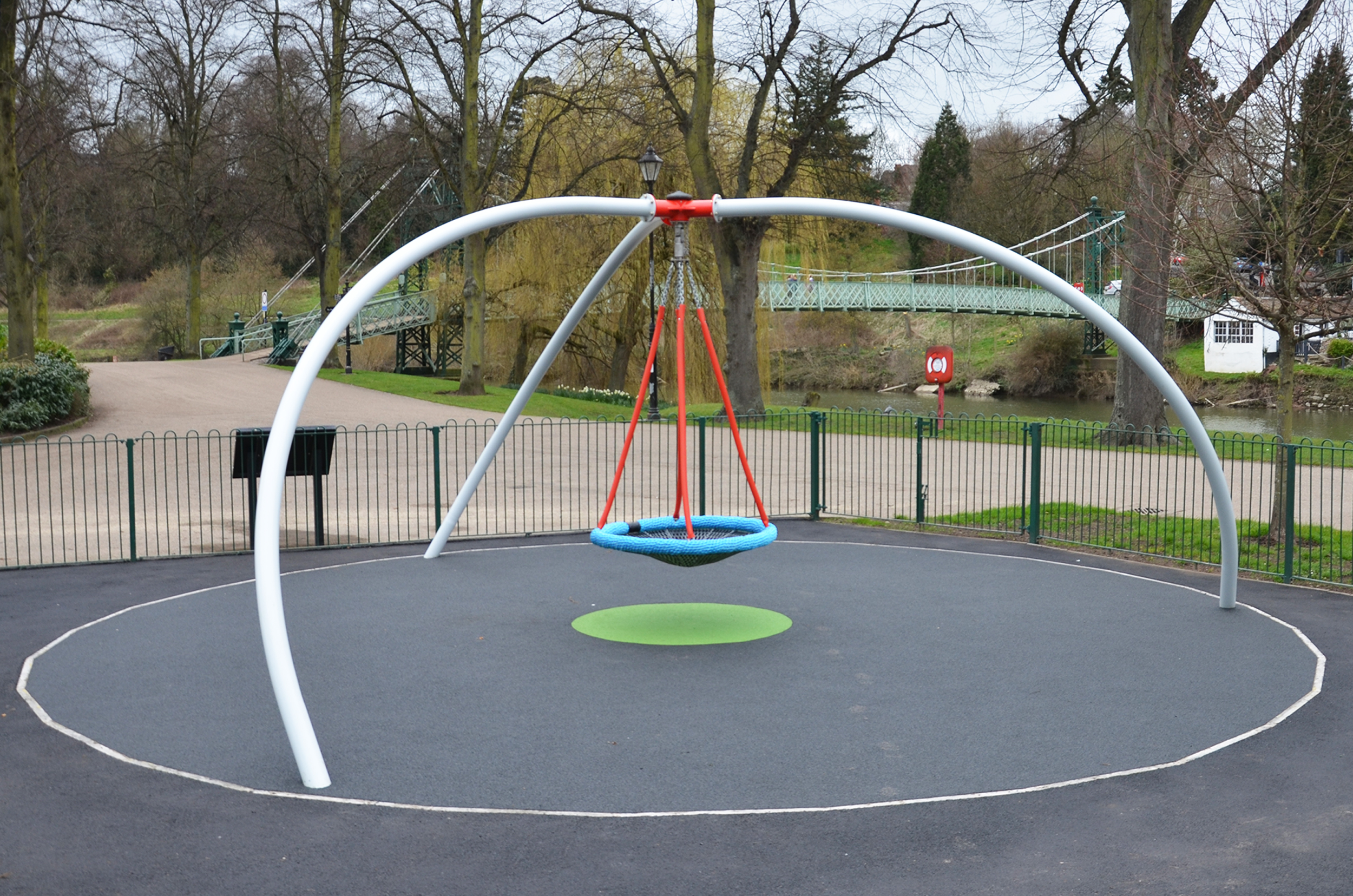the inclusive single point swing has a blue basket seat hanging on chain from a central red pivot held by three curved white legs, it is sat above black rubber surface with a green dot, surrounded by green fencing with trees and a bridge in the background