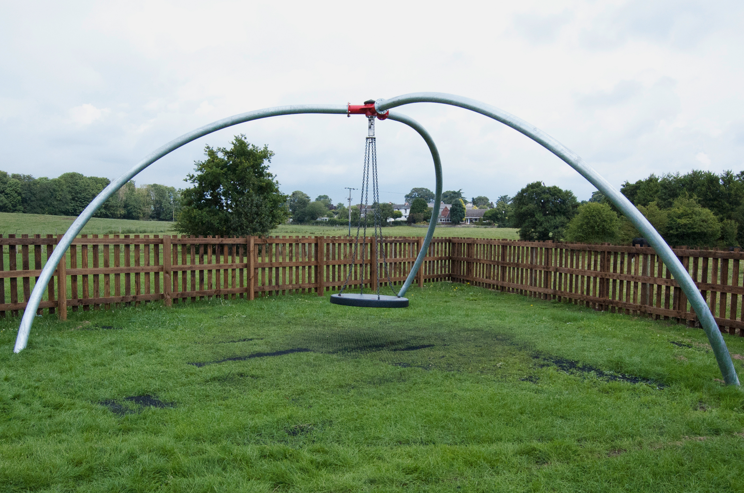 the inclusive single point swing has a flat swing hanging on chain from a central red pivot held by three curved silver legs, it is sat above grass with a surround timber fence and trees in the background
