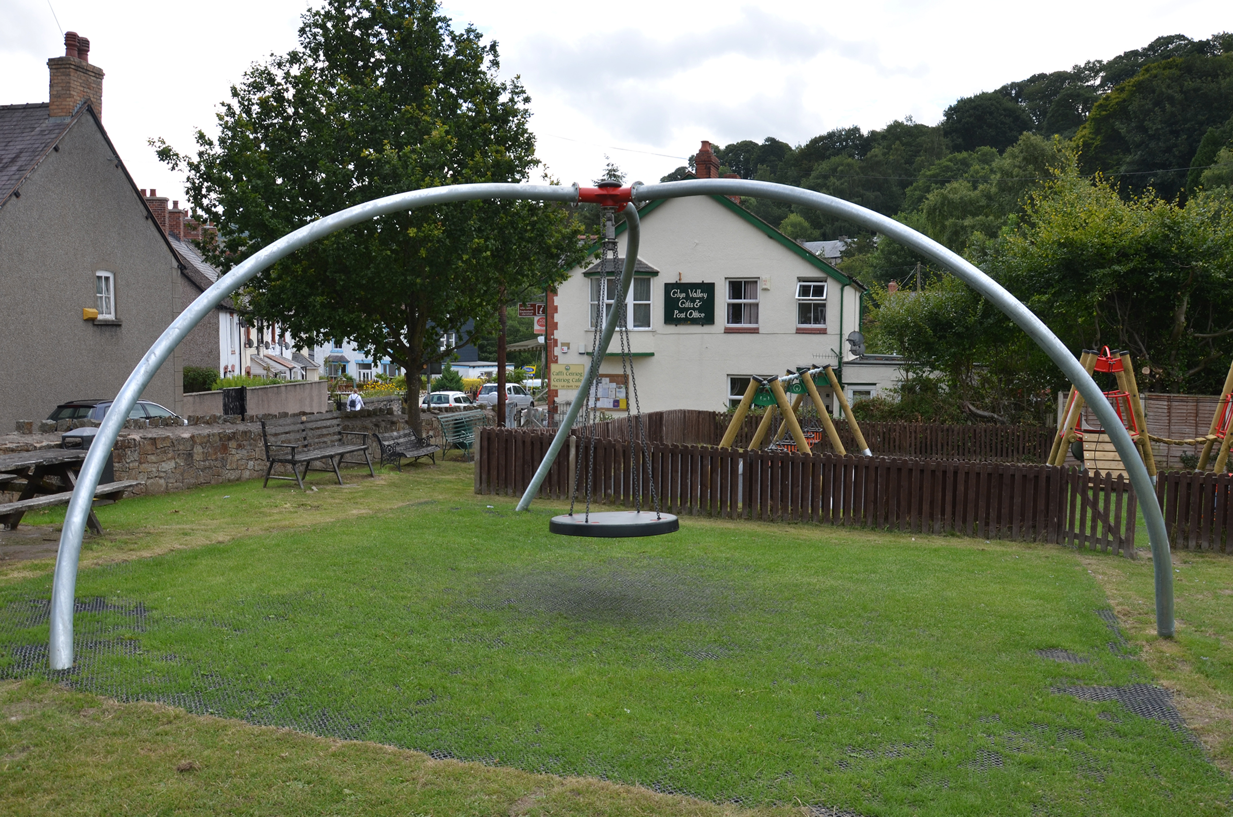 the inclusive single point swing has a flat swing hanging on chain from a central red pivot held by three curved silver legs, it is sat above grass with trees a building and some swings in the background