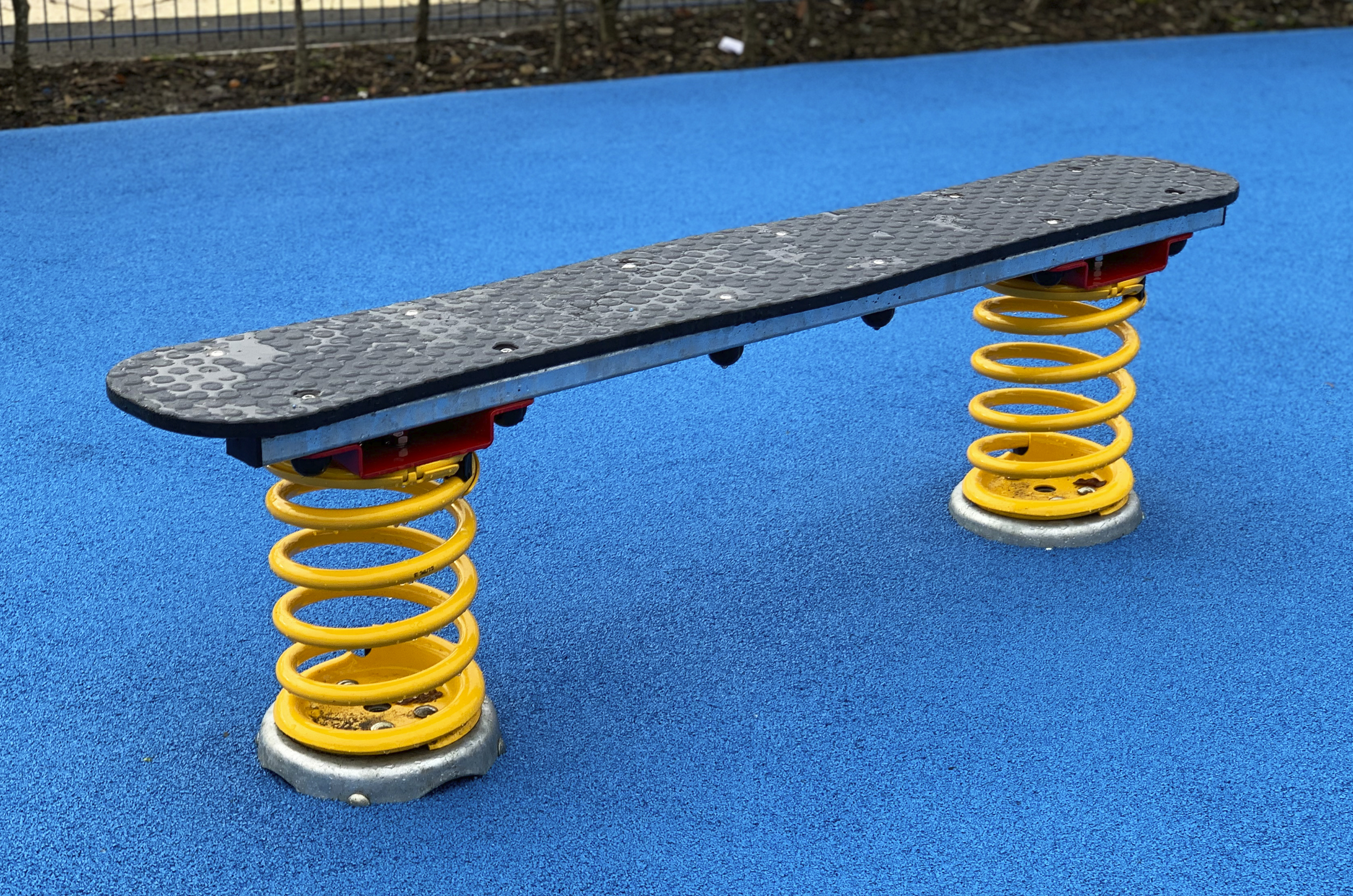 Spring Wobble Board sits on blue wetpour surface, two single yellow springs hold a grey board top