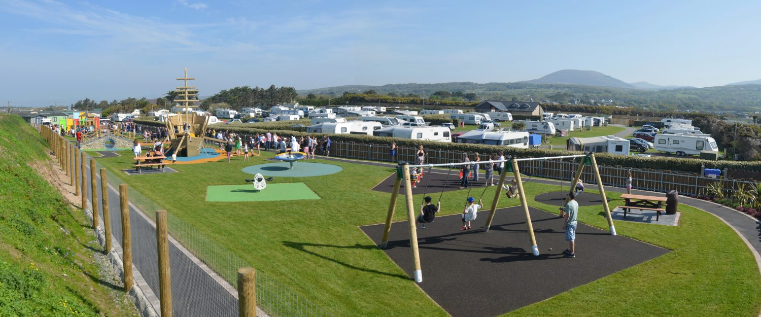 Caravan park playground with green grass, swings, pirate ship & inclusive roundabouts and rotators