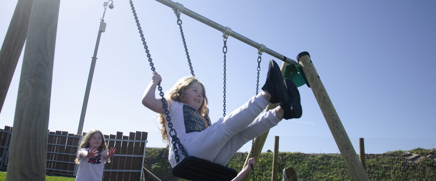 Girl smiling using swing in sunny weather