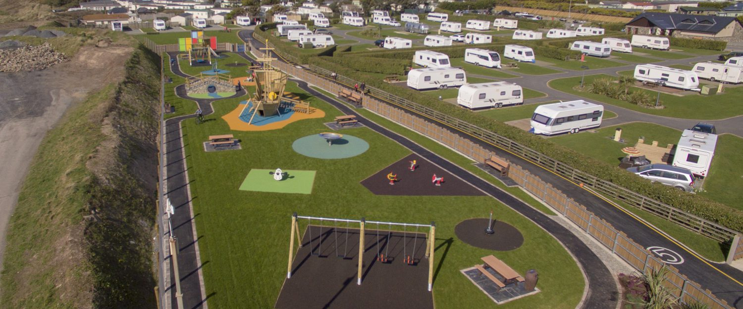 Playground installed into a seaside caravan park with clamber stacks, swings, benches and soft flooring material