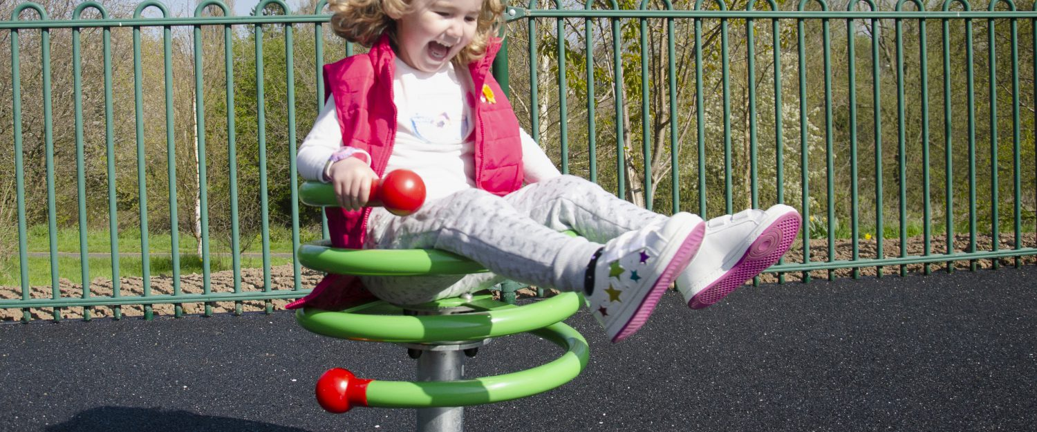 Inclusive rotator equipment with young girl laughing and playing