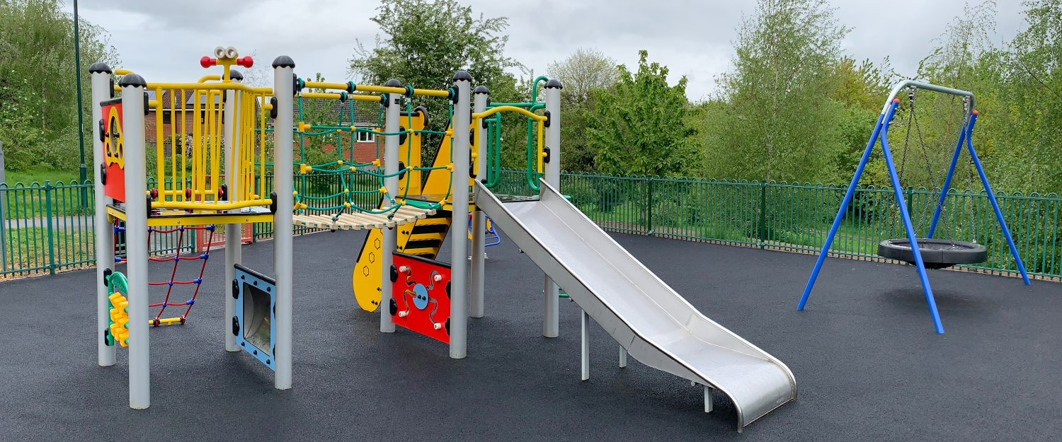 Steel multi play area with slide, play panels, netting bridge, mirrors, puzzle walls along side a steel inclusive rubber basket swing