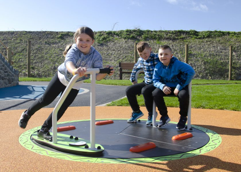 Children playing in leisure holiday park floor level roundabout laughing