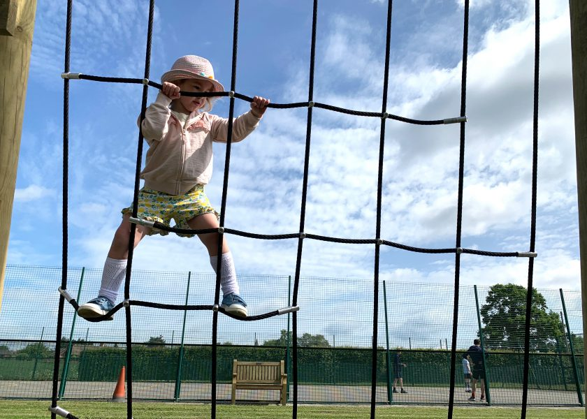 Child playing on nursery playground netting