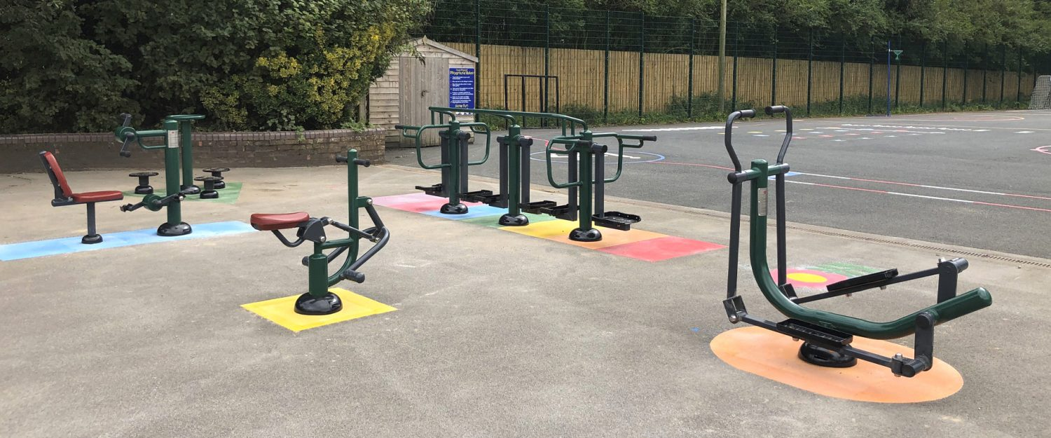 A range of outdoor fitness equipment sit on a playground with multi coloured shapes beneath them