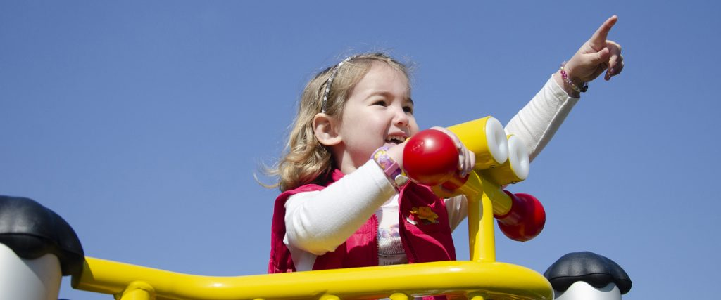 A young child points to the sky from the binoculars of a multiplay climber