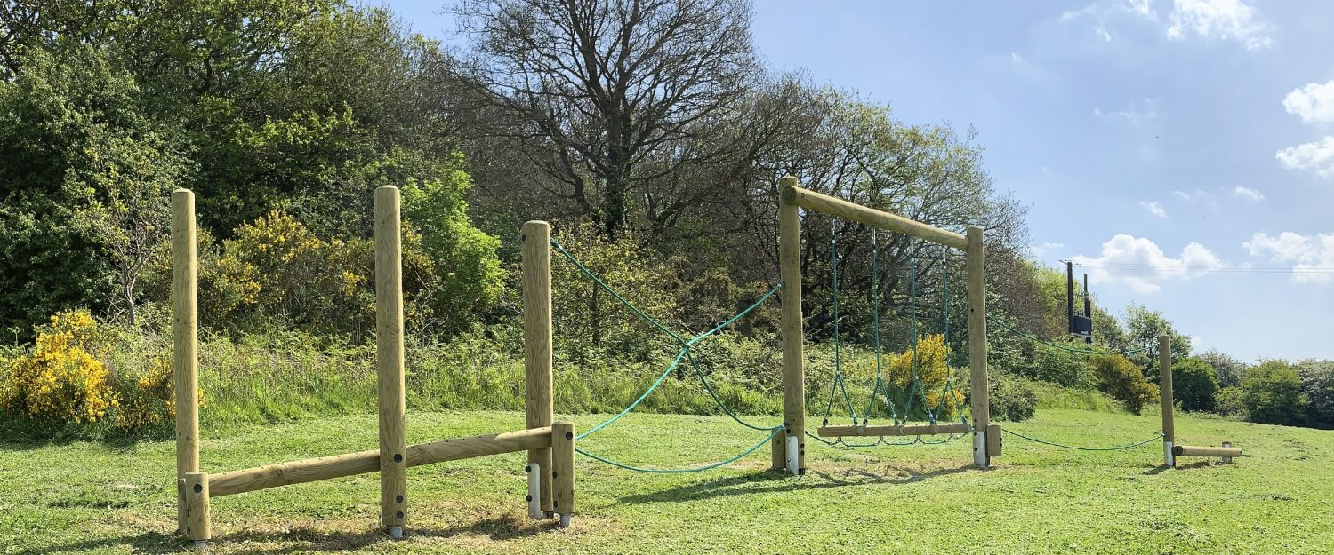 A series of vertical and horizontal timber complete with green ropes create an adventure trail, sitting on green grass with trees in the background