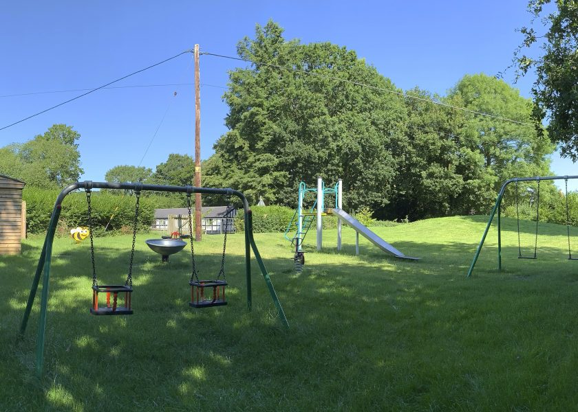 wistanstow play equipment swings, slide, spring riders and spinning dish installed in grass with trees in the background
