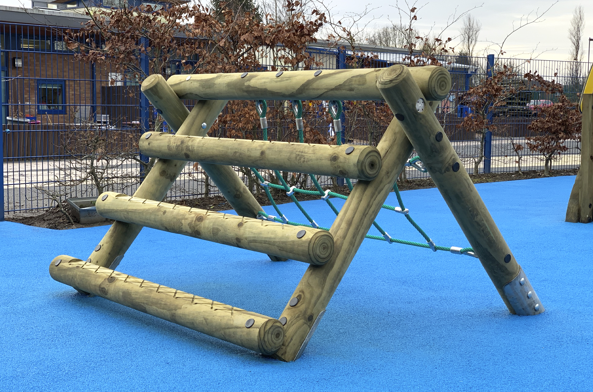 the A Frame Mini is a timber a frame with horizontal logs on the left and a green net on the right side