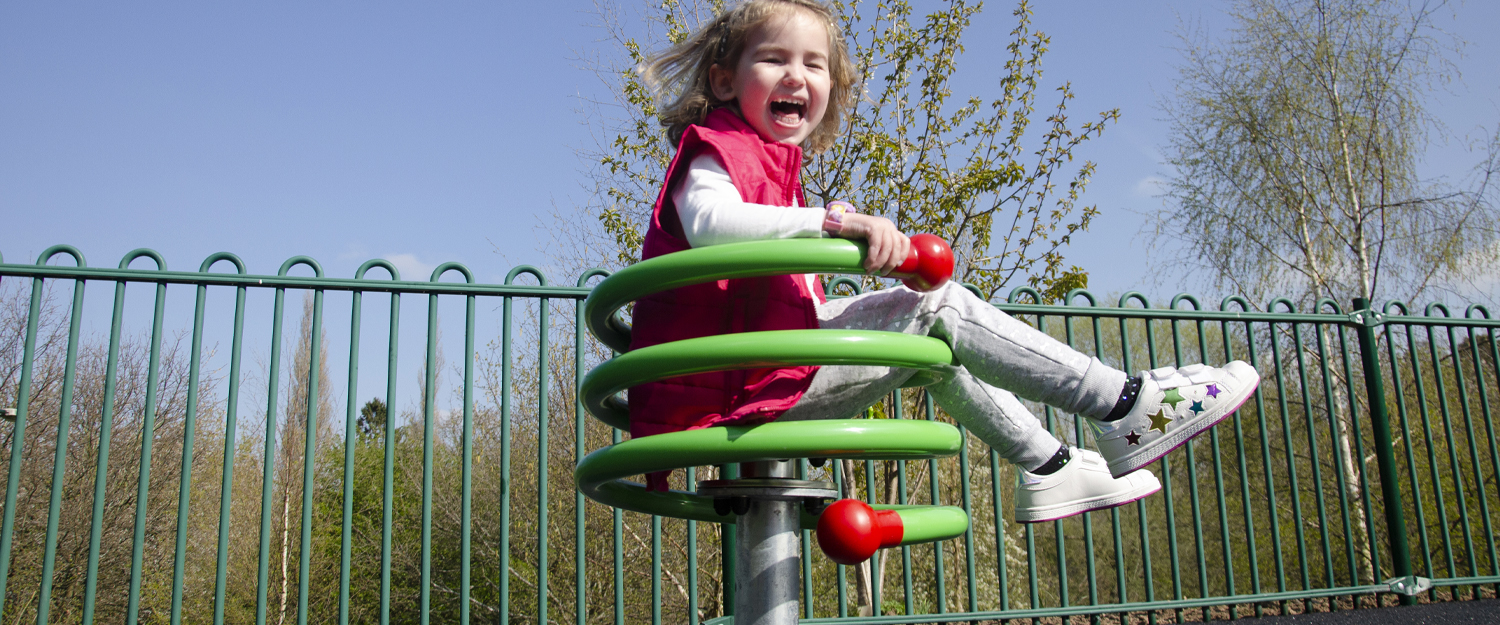 A young girl sits laughing as she spins around on a green curlicue spinner