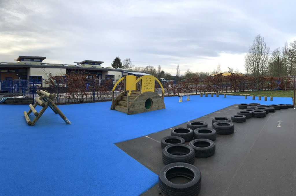 Old Park Nursery Blue Wetpour Safer Surfacing surrounded by tyres with A-frame Mini, Sleeper Tunnel with steps, Spring Wobble Plank, Steeping Logs and Balance Walk