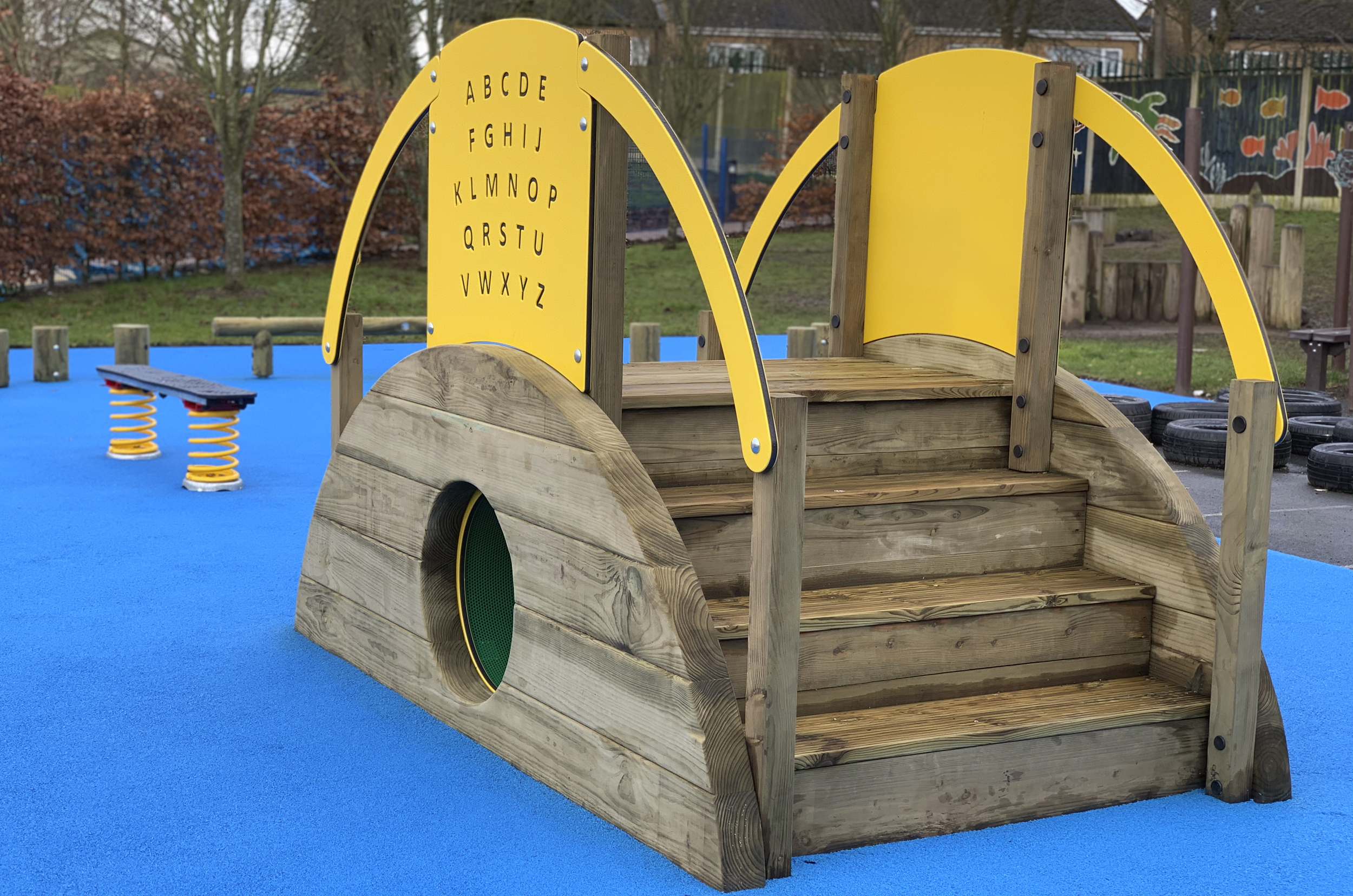 Sleeper Tunnel With Steps, the timber steps sit on the right with the green tunnel entrance at the centre. The yellow play panel show the alphabet