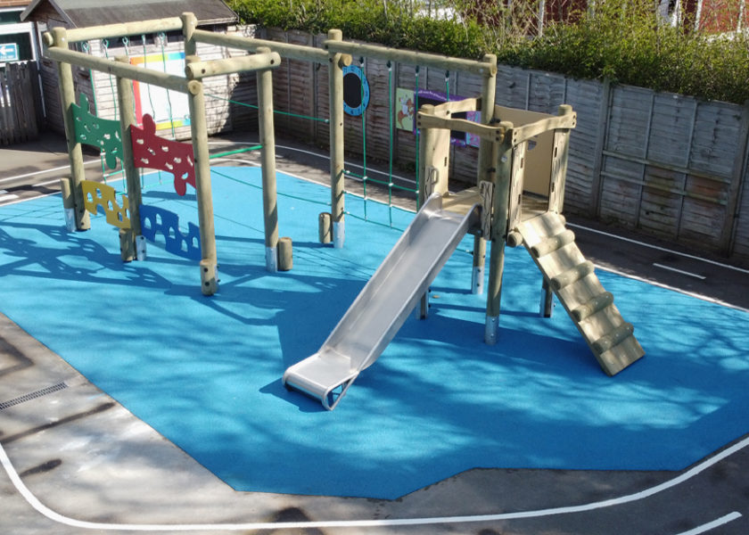 timber climbing frame with slide sit on blue wet pour surface at Trinity CE Primary School