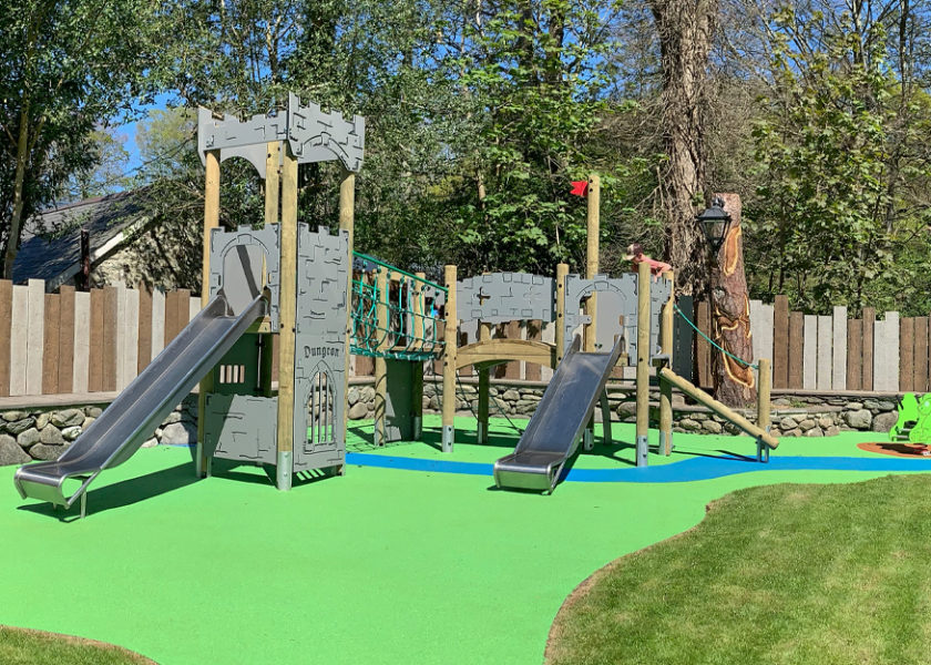 Ysgethin Inn Castle themed play equipment with two slides and dragon spring rider on green and blue wetpour safer surfacing