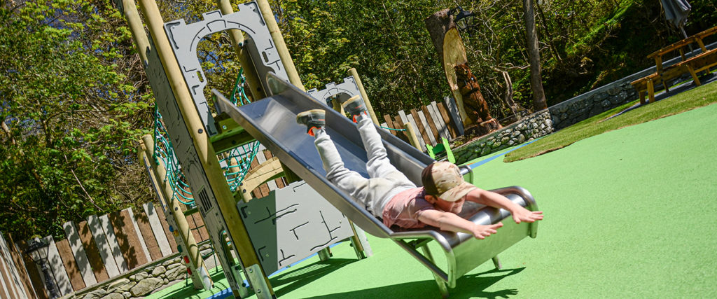 Sliding Into Summer with Ray Parry Playgrounds - A boy slides head first down a slide surrounded by green safer surfacing