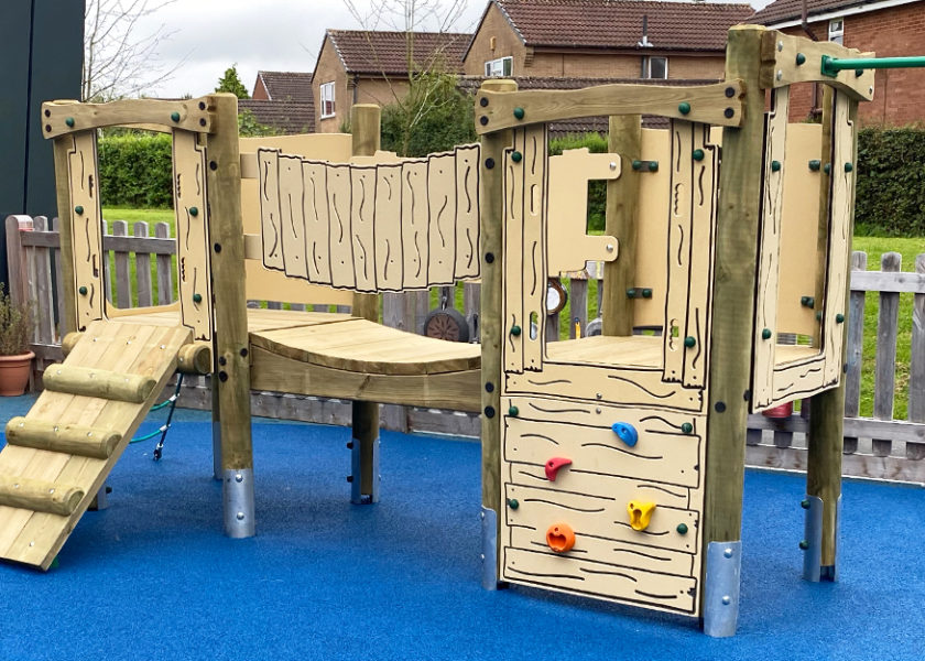 Ladygrove School - Timber climbing frame sits on blue wetpour safer surfacing