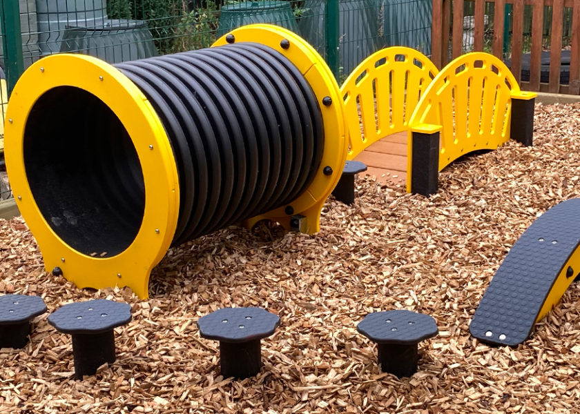 Fun Adventure Trail with yellow and black play equipment with wood chip safer surfing flooring